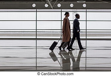 Elegant woman is carrying baggage with her colleague male