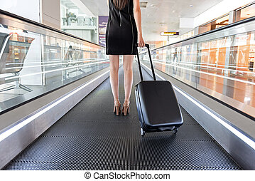 Elegant woman is holding her luggage on escalator