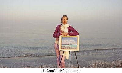 Motion to woman wearing white scarf and violet cardigan on sea beach leaning on easel with amazing seascape in pastel colors