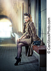 Elegant woman on bench thinking