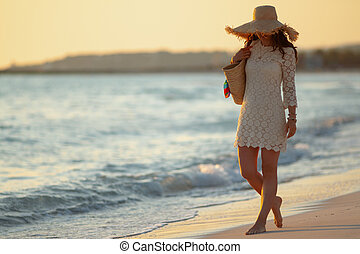 elegant woman on ocean coast at sunset walking