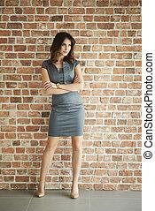 Elegant woman on the brick wall