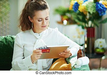 elegant woman ordering medicine online on tablet PC