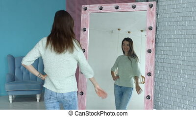 Elegant woman posing in front of mirror at home
