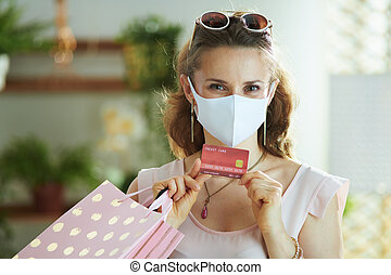 elegant woman shopper with mask, credit card and bags