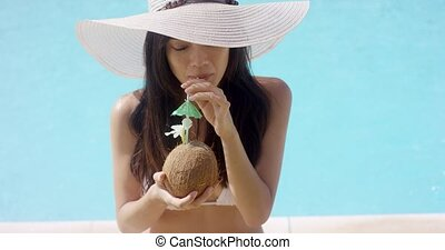 Elegant woman sipping a tropical cocktail - Elegant woman in...
