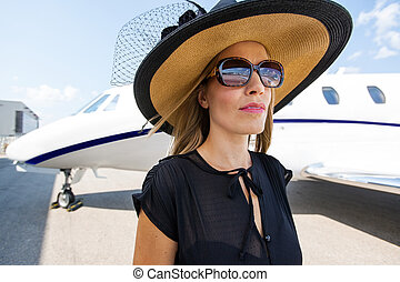 Elegant Woman Standing Against Private Jet