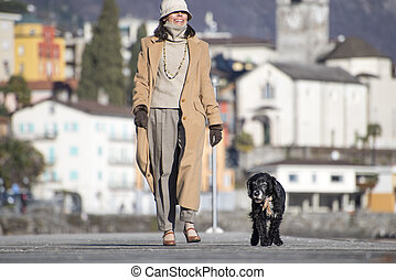 Elegant woman walking on the street with her dog