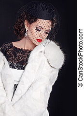 Elegant woman wearing in white fur coat isolated on black background
