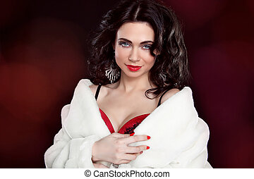 Elegant woman wearing in white fur coat over dark