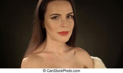 Elegant woman wearing white fur jacket and sexy short black bodycon dress