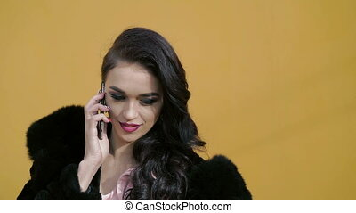 Elegant woman with blue eyes in the fur speaking on the smartphone