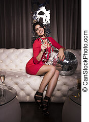 Elegant woman with champagne flute sitting on sofa