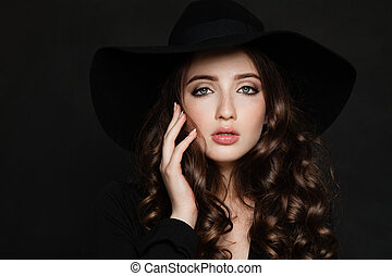 Elegant Woman with Makeup, Curly Hair and Manicured Hand. Beautiful Model in Black Hat