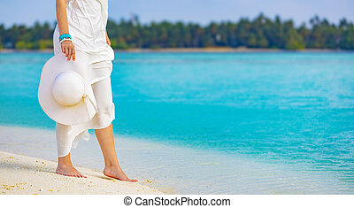 Elegant woman with pareo and hat relaxes walking on the white sand of a beach in the Maldives