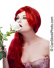 elegant woman with red hair smelling a bouquet of white roses