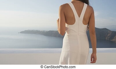 Elegant young woman holding red wine glass outside walking at terrace in luxury villa enjoying beautiful sea view and mountains. Female in white sundress on summer vacation travel. Santorini, Greece.