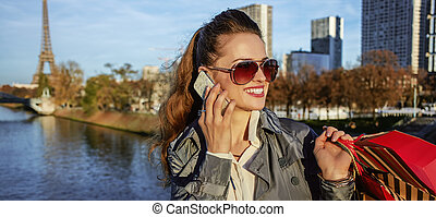 elegant woman with shopping bags speaking on mobile in Paris...