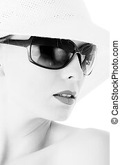 Elegant woman with sun glasses and white hat. BW