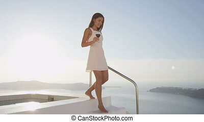Elegant woman in luxury villa outdoors drinking red wine. Smiling young woman holding wine glass walking by swimming pool. Female in white sundress enjoying beautiful view of nature, Santorini. Greece