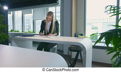 Elegant woman working in stylish office. Modern blond woman in trendy suit sitting at table in light contemporary office and writing on papers.