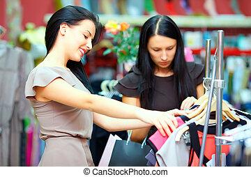 elegant women shopping in retail clothing store
