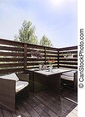 Elegant wooden balcony with garden furniture