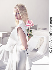 Elegant, young blonde holding a beautiful pink rose