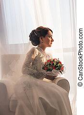 Elegant young bride in wedding dress, studio shot