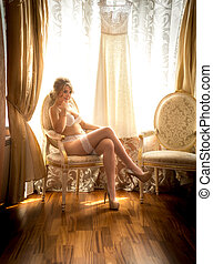 young bride in white lingerie posing on chair at hotel room