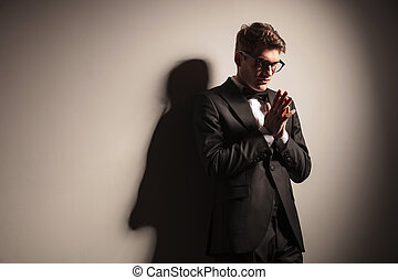 Elegant young business man praying.