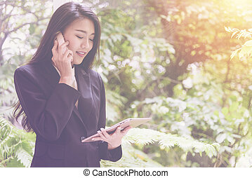 Elegant young business woman using tablet and talking on the phone stand by the window for relax, looking at screen