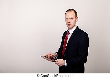 elegant young businessman keeps the tablet in hands, watching straight