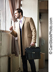Elegant young businessman looking out the window.