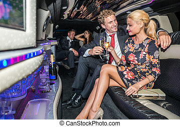 Elegant young couple toasting champagne flutes in limousine
