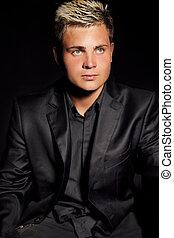 Elegant young handsome man over dark. Studio fashion portrait.