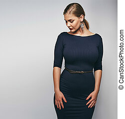 Studio image of elegant young lady in black dress. Oversized and curvy female model on grey background.