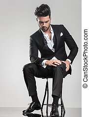 Elegant young man stitting on a stool while looking down - ...