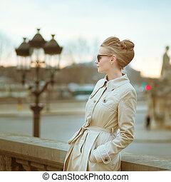 Elegant young Parisian woman outdoors.