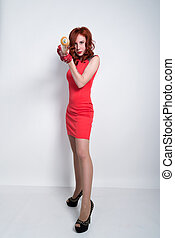 Elegant young redhead woman in little red dress and red leather gloves, brandishing a baseball bat