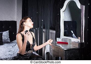 Elegant young woman applying perfume