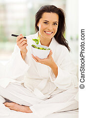 elegant young woman eating salad