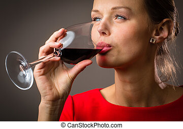 Elegant young woman having a glass of red wine