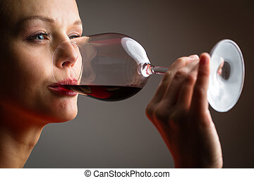 Elegant young woman in a red dress, having a glass of red wine