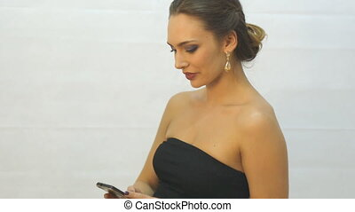 Elegant young woman in black evening gown looking at...