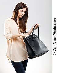 Elegant young woman looking in her bag