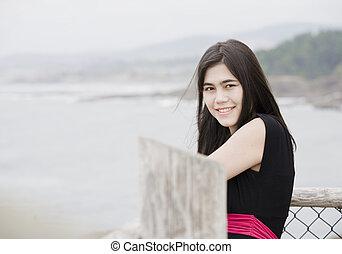 Elegant young woman or teen standing by ocean in simple black dress