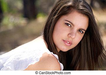 Elegant young woman posing outdoors