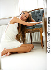 Elegant young woman resting on chair
