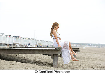 Elegant young woman sitting by the seaside